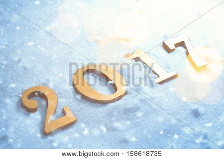 Golden 2017 figures in the snow, Christmas and new year concepts