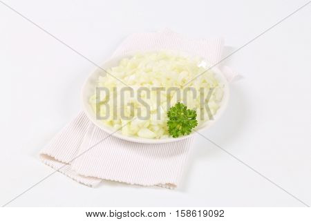 plate of chopped raw onion on white place mat
