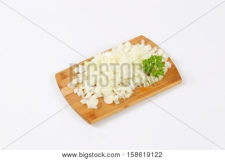 pile of chopped raw onion on wooden cutting board