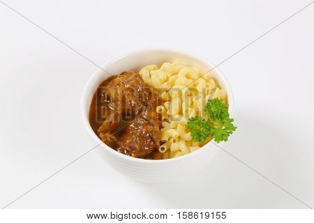bowl of fresh beef goulash with cooked rigatoni pasta