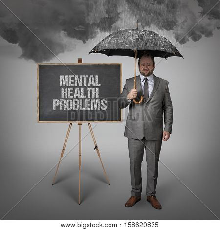 mental health problems text on blackboard with businessman holding umbrella
