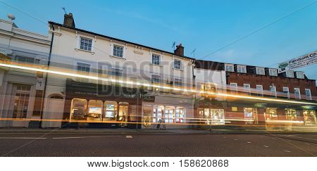 Farnham/UK. 26th November 2016. Shops and retail facilities in a historic central Farnham Street at twilight on a winter's evening. Cars are captured as light trails on a long exposure.