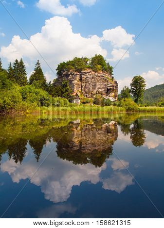 Rock castle Sloup v Cechach reflected in the water on sunny day, Northern Bohemia, Czech Republic