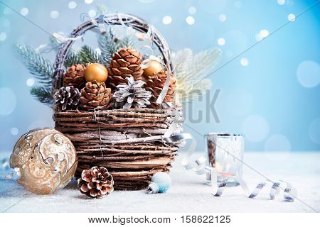 Decorations for Christmas and New Year. Old basket with cedar and pine cones and christmas balls and candles. Christmas holiday background