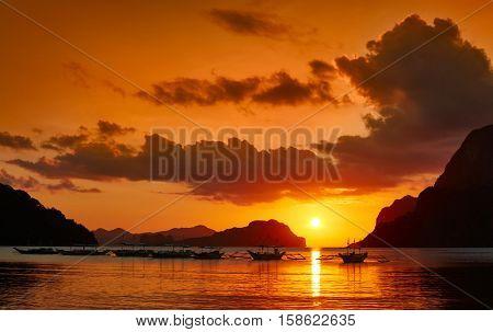 Palawan island, Philippines. Traditional filippino boats at El Nido bay in sunset lights.