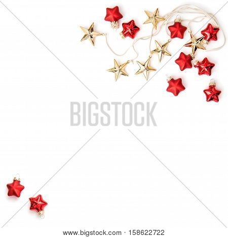 Christmas ornaments and decorations. Golden stars and red baubles on white background. Minimal flat lay