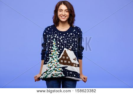 Young cheerful beautiful brunette girl in cosy knited sweater smiling posing over blue background. Copy space.