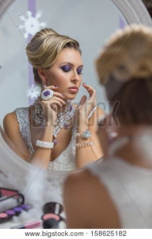Beautiful young woman with bright purple makeup and fancy hairdo sitting in front of mirror. Gorgeous winter bride.