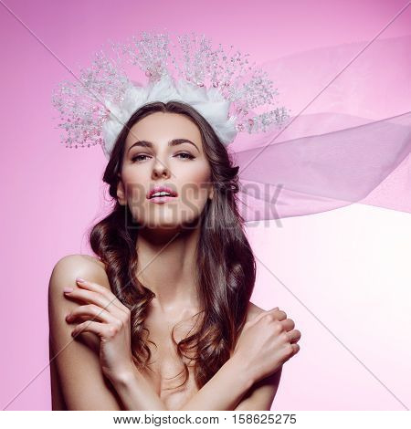 Beautiful young brunette woman in crystal crown and white veil touching face on pink background. Romantic beauty look. Copy space.