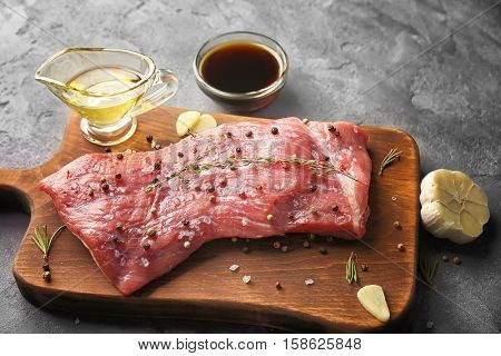 Tasty steak with marinade ingredients on board and grey background
