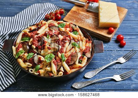 Pan with tasty macaroni, napkin, kitchen board and forks on wooden table