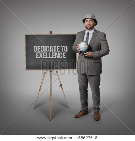 Dedicate to exellence text on blackboard with businessman holding globe in hands
