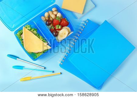 Tasty sandwich and fruits in lunchbox and stationery on blue background