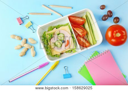 Tasty dinner in lunchbox and stationery on blue background