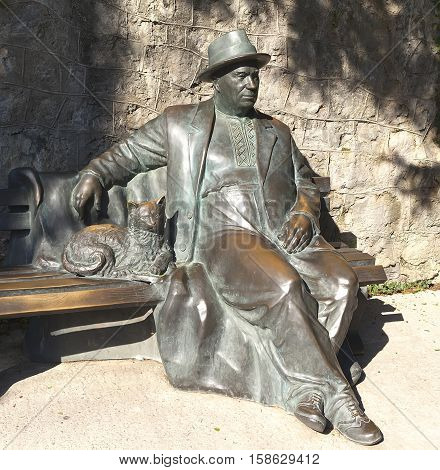 Partenit, Crimea - September 7, 2016: A bronze sculpture of a man dressed in a coat and hat, sitting on a bench and stroking a cat. The sculpture Resting krymchanin . The collective image of a man resting in a sanatorium. Established in the summer of 2013