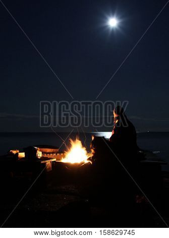 Woman and dog at a fire pit at seashore during full moon