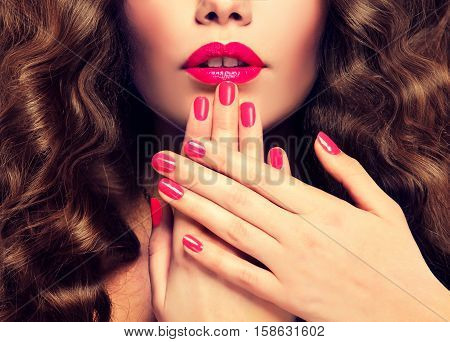 Beautiful girl  long , thick curly hair . Model showing a pink  manicure on nails and lips  .