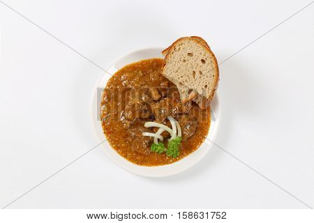 plate of fresh beef goulash with slices of bread