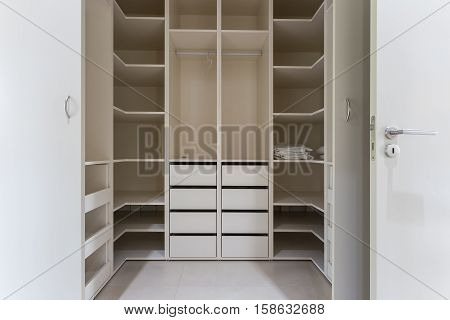 Modern apartment interior with huge wardrobe. White.