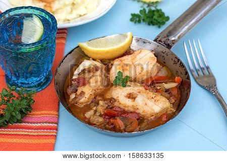 Fish in vegetable marinade with pepper and tomatoes and mashed potatoes