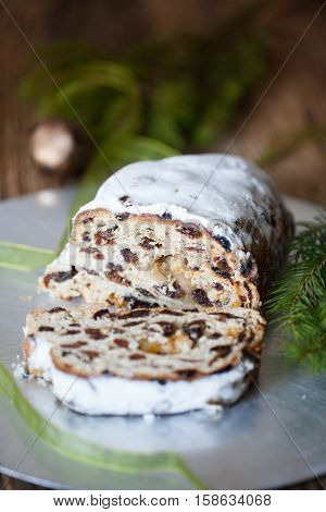 Christmas stollen. Traditional German, European festive dessert. Ingredients cranberries, pine nuts for Christmas Stollen. Stollen cake cut into pieces. Christmas food card.