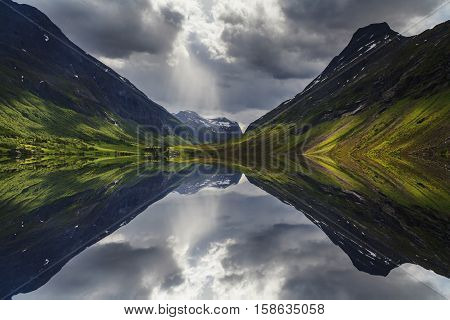 Misty mountains at dawn. Reflection in the lake