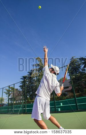 Professional tennis player is doing a kick tennis on a tennis court on a sunny summer morning. He is dressed in sportswear.