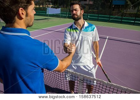 Two men, professional tennis players shake hands before and after the tennis match. One of they has the face of anger. He is trying to intimidate his opponent.