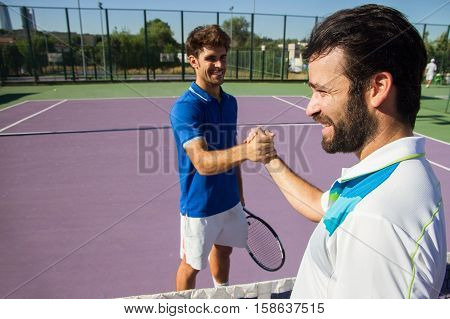 Two men, professional tennis players shake hands before and after the tennis match. Both are laughing, they are happy. They are friends.