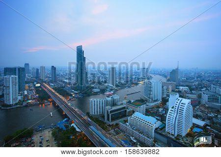 top view of bangkok skyscraper and traffic crossing chaopraya river in heart of capital