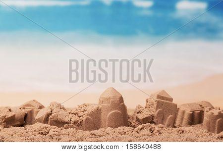 Battered sandcastles on the sunny ocean background