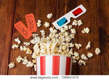 Loose popcorn in striped box, two tickets to the cinema and 3D glasses on a wooden background