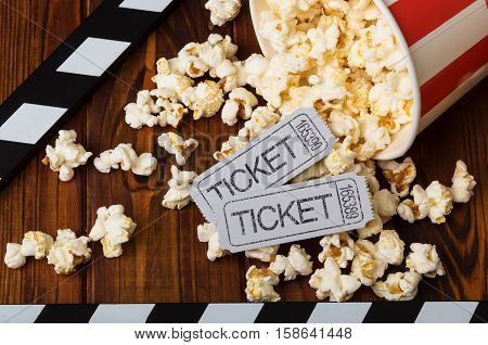 Clapper board, spilled popcorn and movie tickets on a background of boards