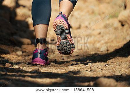 Cross country running feet run through rocky terrain,view from behind