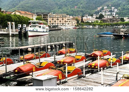 ITALY. COMO - APRIL 21, 2016: Pleasure yachts and boats at the pier on the waterfront of Lake Como on the background of the Alps.