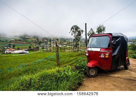 Auto rickshaw tuk-tuk on vegetable plantation. Foggy day.