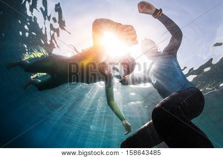 Underwater shot of the freedivers training static breath hold in shallow water of a calm bay. Coach watching student