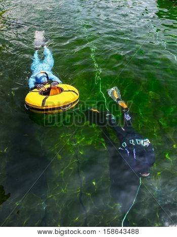 Free divers training with buoy in the swimming pool with green moss bottom