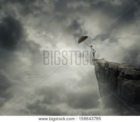 Boy trying to catch his umbrella on the edge of a cliff above the clouds. Escape and fly away.