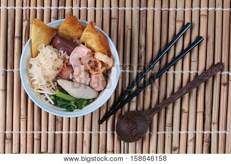 Thai noodle with pink tofu soup topped rugby fishball ,wonton,porkball,boiled porkblood,pork rind,coriander and white mushroom call Yen Ta Fo in Thai