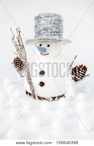 Large handmade snowman surrounded by white iridescent snowballs on white background.