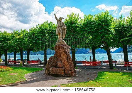 Lugano, Switzerland - August 25, 2013: Sculpture of William Tell at the promenade of the luxurious resort in Lugano on Lake Lugano and Alps mountains in Ticino canton of Switzerland.