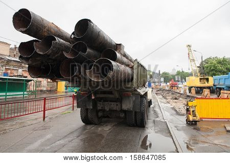 Truck transports old pipes in the construction area. Kyiv Podil.
