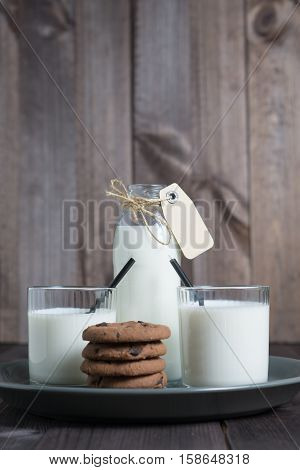 bottle of milk with carton label tag with two transparent glass, black straw and pile brown cookies in gray plate on dark wooden background