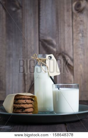 bottle of milk with carton label tag with one transparent glass, black straw and pile brown cookies in gray plate on dark wooden background