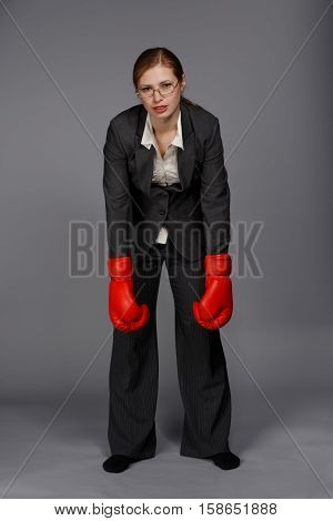 Tired irresolute young blonde woman in dark grey business suit glasses and red boxing gloves stands in despair pose with her hands down on grey background.