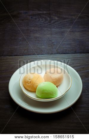 Beautiful mango mochi rice cakes on white ceramic plate standing on vintage wooden table.