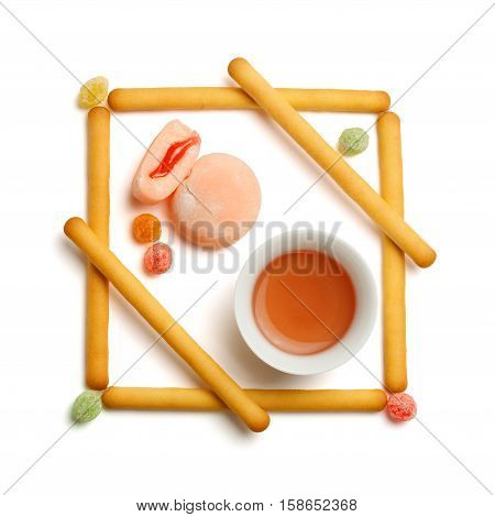 Minimalist geometrical composition of biscuit cookie sticks colorful fruit drops tea in chinese cup and mochi rice cakes with fruit filling isolated on white background. Top view.