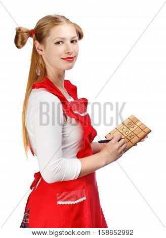 Young beautiful smiling housewife in red apron with funny ponytails holds pen and wooden cutting board with tic-tac-toe drawed on it isolated on white background.