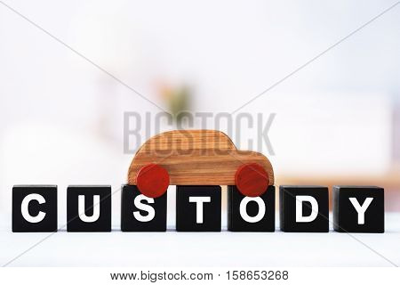 Cubes with word CUSTODY and toy car on blurred background